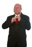 Man in Tux. Middle aged man in black tux, fixing his tie, isolated on white Stock Photos