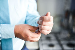 Man in a tux fixing his cufflink Stock Photo