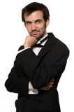 Man in tuxedo. Attractive young brunette man with a beard wearing a black tuxedo posing with hand on chin Stock Images