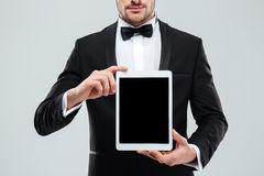 Man in tuxedo with bowtie holding blank screen tablet Stock Photos