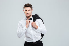 Man in tuxedo with bowtie standing and holding his jacket Royalty Free Stock Image