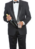 Man in Tuxedo with Champagne. Man wearing a tuxedo and holding a bottle of Champagne isolated over white - torso only Royalty Free Stock Images