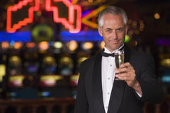 Man in tuxedo drinking champagne in casino. Proposing toast Stock Photo