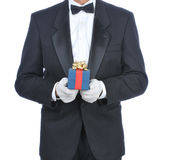 Man in Tuxedo with Gift. Man wearing a tuxedo and holding a gift box isolated over white - torso only Royalty Free Stock Photography