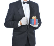 Man in Tuxedo with Gift. Man wearing a tuxedo and holding a gift box isolated over white - torso only Royalty Free Stock Photo
