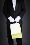 Man in Tuxedo with Gift Bags. Closeup of a gentleman in a tuxedo holding two gift bags. Vertical format on a light to dark gray background. Man is unrecognizable Royalty Free Stock Photos
