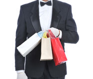 Man in Tuxedo with Gift Bags. Man wearing a tuxedo and holding a gift Bags isolated over white - torso only Royalty Free Stock Image