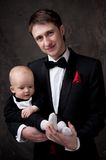 Man in tuxedo holding his son Royalty Free Stock Photo