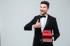 Man in tuxedo holding present box and showing thumbs up Stock Image
