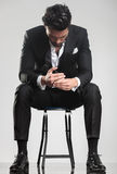 Man in tuxedo looking down while sitting on a stool, Stock Photos