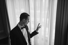 A man in a tuxedo looking out the window. Stock Photography
