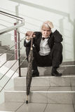 A man in a tuxedo on a metal ladder. Man in stress to be on high metal ladder royalty free stock image