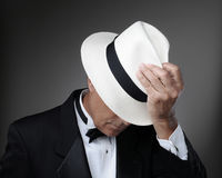 Man in Tuxedo with Panama Hat. Closeup of a middle aged man wearing a tuxedo and a Panama Hat. Horizontal over a gray background Royalty Free Stock Images