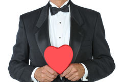 Man-in Tuxedo with Red Heart. Man in Tuxedo Holding a Red Heart Shaped Candy Box isolated over white Stock Images