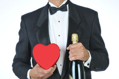 Man-in Tuxedo with Red Heart and Champagne. Man in Tuxedo Holding a Red Heart Shaped Candy Box and a Bottle of Champagne isolated over white Royalty Free Stock Photo