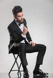 Man in tuxedo sitting on a stool snapping his finger Royalty Free Stock Photos