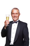 Man in tuxedo toasting with champagne. A mature male wearing a black tuxedo and bow tie raising a glass of champagne, isolated on a white background Royalty Free Stock Photos