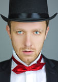 Man with tuxedo and top-hat. Closeup portrait of a young man wearing a formal tuxedo, red bow tie and black top-hat Stock Images