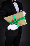 Man in Tuxedo wiht Present. Closeup of a gentleman in a tuxedo holding a Christmas present under his arm. Vertical format on a light to dark gray background. Man Stock Photos