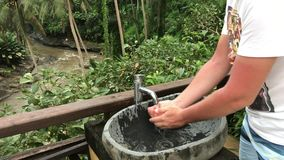 Man tvätt av hans händer utanför med en härlig tropisk sikt Friskhet- och ekologibegrepp Bali ö stock video