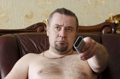 Man with a TV remote control. On sofa in the room Stock Photos
