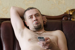 Man with a TV remote control. On sofa in the room Stock Photo