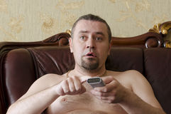Man with a TV remote control. On sofa in the room Royalty Free Stock Images