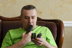 Man with a TV remote control. Man with three TV's remote control Stock Photography