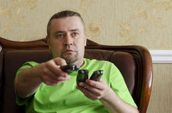 Man with a TV remote control. Man with three TV's remote control Royalty Free Stock Images