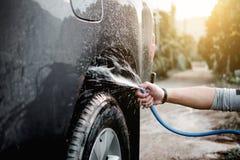 Man tvagning- och lokalvårdbilen med att bespruta pressat vatten arkivbild