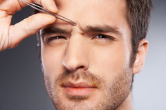 Man tweezing eyebrows. Stock Images