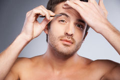 Man tweezing his eyebrows. Stock Images