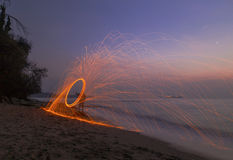 Man twirling fireworks on beach Stock Photo