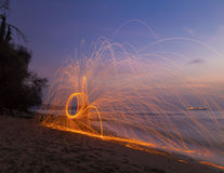Man twirling fireworks on beach Stock Photography