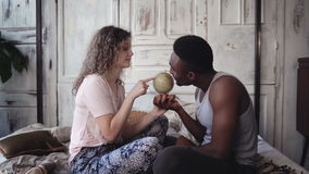 Man twist the globe, woman points with finger the location to traveling. Multiracial couple picking destination to trip. African men twists the globe, caucasian royalty free stock photo