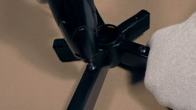 A man twists into piece of revolving chair using screwdriver.  stock footage