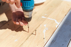The man twists the screws into the boards using a screwdriver Royalty Free Stock Images