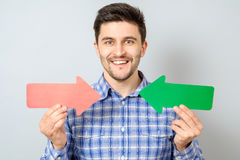 Man with two arrows pointing to the right and left. On gray Royalty Free Stock Images