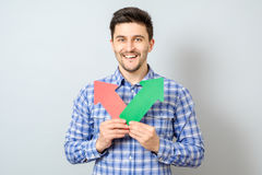 Man with two arrows pointing to the right and left. Isolated on gray Stock Images