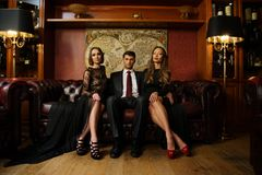 Man with two beautiful women. Handsome brunette wearing suit sitting on sofa with two beautiful women Stock Photography