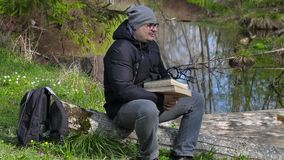 Man with two books relaxing in meadow near river stock footage