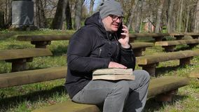 Man with two books and smart phone on bench in park stock video