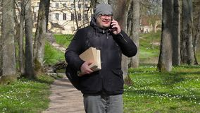 Man with two books talking on smart phone and walking in the park. In summer day stock video
