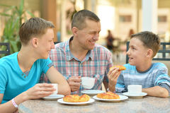 Man and two boys having breakfast Stock Images