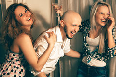 Man with two charming girls laughing at a party Stock Image
