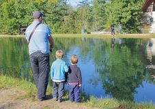 a man and two children fishing. Father and two sons fishing, trout at a trout farm. Children watch as fish.. stock images