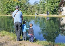 a man and two children fishing. Father and two sons fishing, trout at a trout farm. Children watch as fish.. stock photo