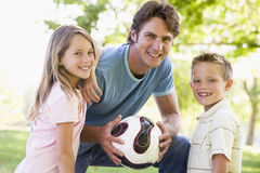 Man and two children outdoors holding volley. Man and two young children outdoors holding volley looking into camera royalty free stock image
