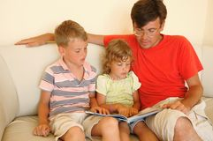 Man and two children read book. Sitting on sofa Stock Photos
