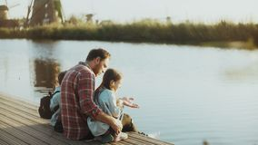 Man with two children sit and talk on river pier. Single father building his family. Bringing up new generation. 4K. Man with two children sit and talk on river stock footage